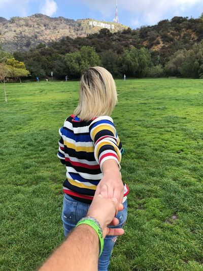 Couple holding hands on field against trees