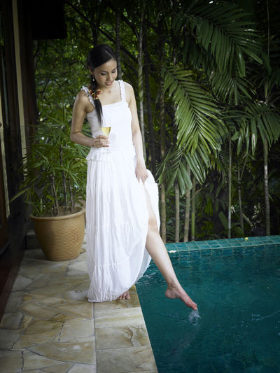Young Woman Holding Champagne Flute While Standing At Poolside