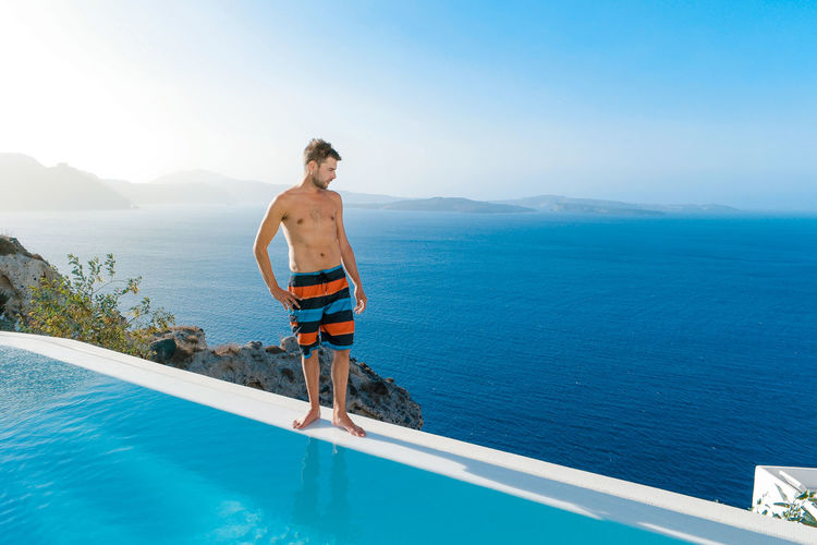 Shirtless man standing on poolside by sea against blue sky