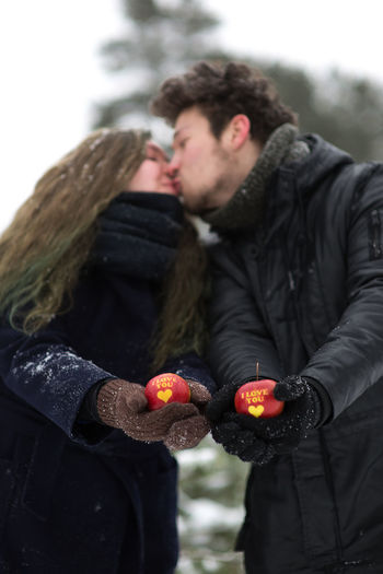 Young couple holding apples with text while standing in forest during winter