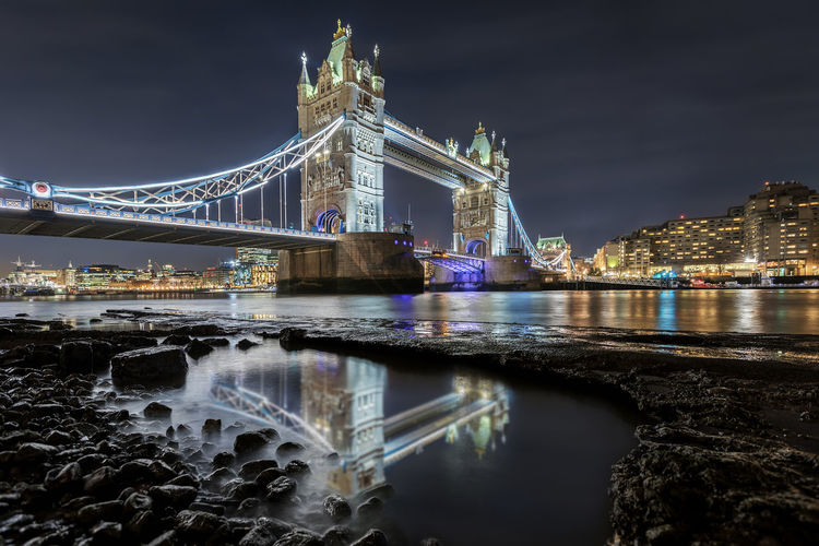 Low angle view of illuminated tower bridge over thames river at night