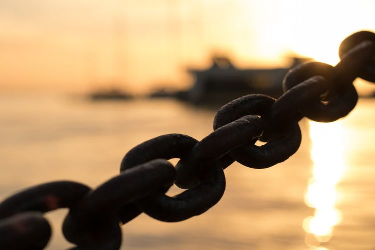 Close-up of silhouette chain on beach against sky during sunset