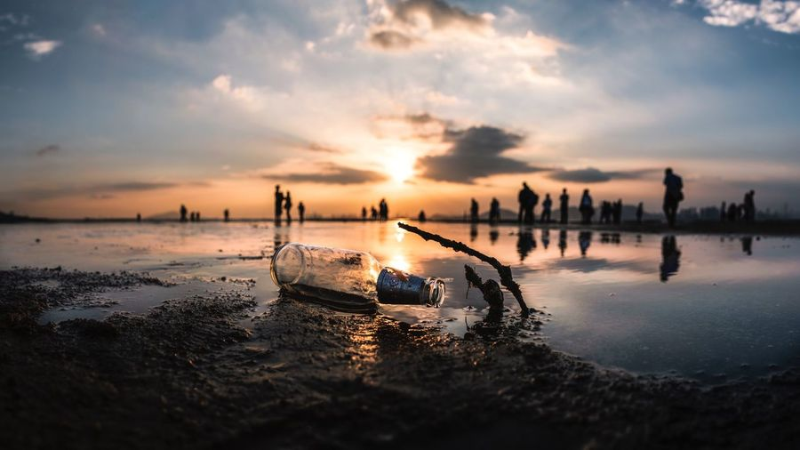 Close-up of empty bottle at beach against sky during sunset