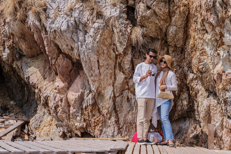 Portrait of couple standing on boardwalk against rock formation
