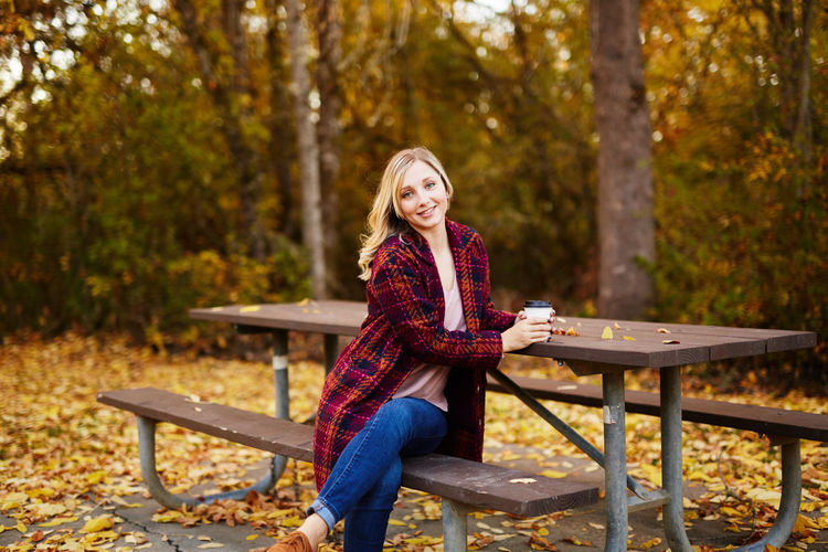 Young woman sitting on picnic table in park during autumn