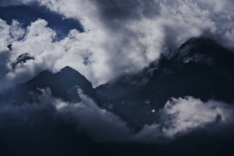 Low angle view of clouds over mountains