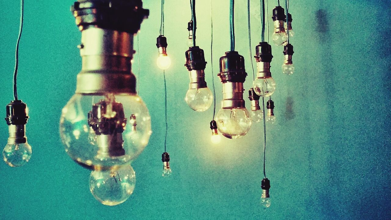 light bulb, electricity, hanging, no people, indoors, close-up, filament, illuminated, technology, day
