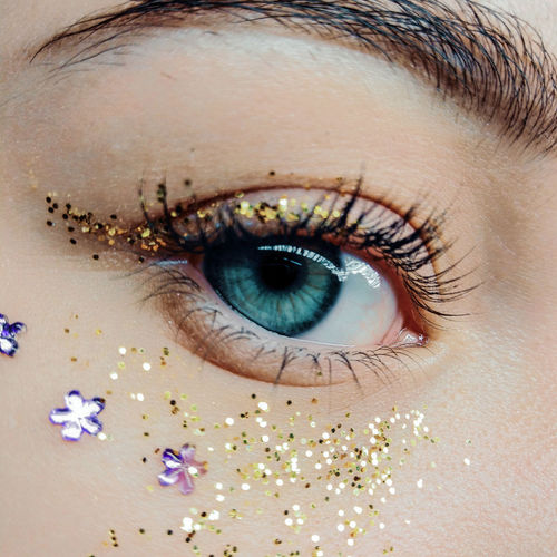 Close-up of girl eye with decoration and glitters