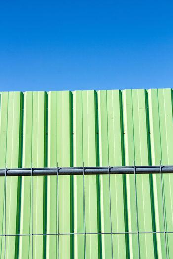 Full frame shot of green metal fence against blue background
