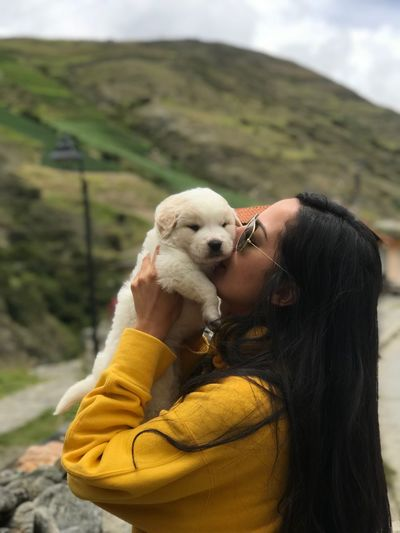 Woman Kissing Dog Against Mountains