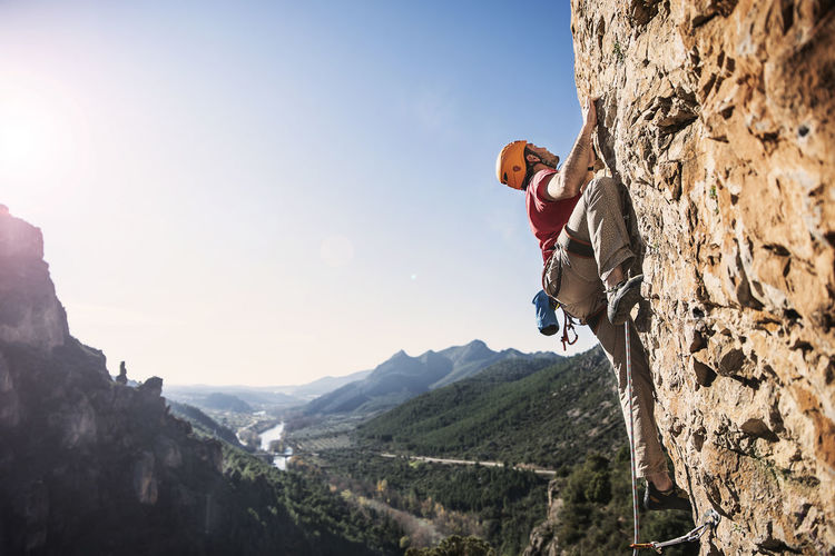 the challenge Mountain Climbing Adventure One Person Rock Climbing Sport Extreme Sports Activity Leisure Activity Sky Nature Mountain Climbing Rock Formation Mountain Range Sunlight Real People Outdoors Lens Flare Effort Skill  Brave Adventurous Climber No Fear Challenge