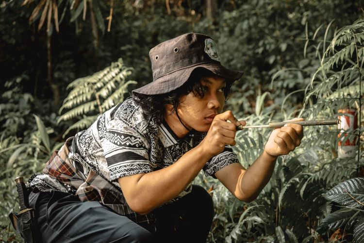 Young man wearing hat holding toy against plants in forest