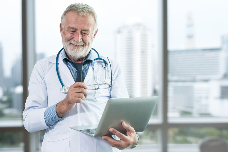 Smiling Senior Doctor Using Laptop While Working In Hospital