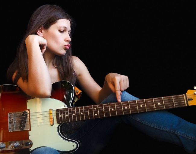 Young woman with guitar against black background