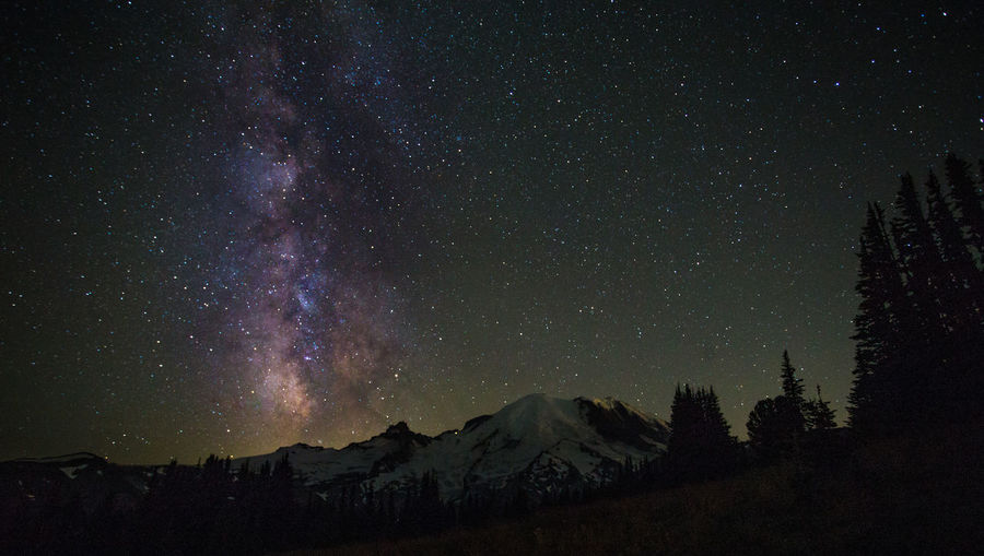 Low angle view of mountain against star field