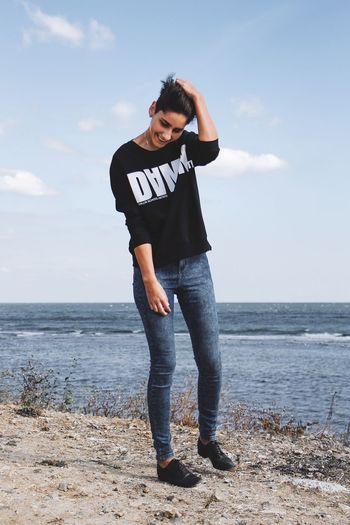 Full length of teenage girl standing on beach against sky