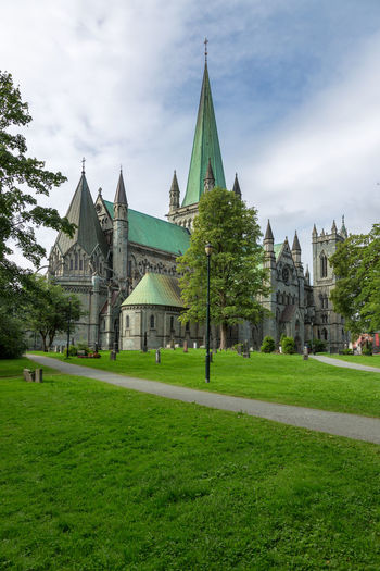 Urban landscape in Norway,Trondheim Cathedral Cityscape Nidaros Cathedral Nidarosdomen Norway Travel Trondheim Architecture Belief Building Building Exterior Built Structure Cathedrale Cityscape Photography Cloud - Sky Day Grass Green Color Incidental People Lawn Nature Nidaros Nidaros Cathedral Norway Nature Outdoors Place Of Worship Plant Religion Sky Spire  Spirituality Travel Destinations Tree