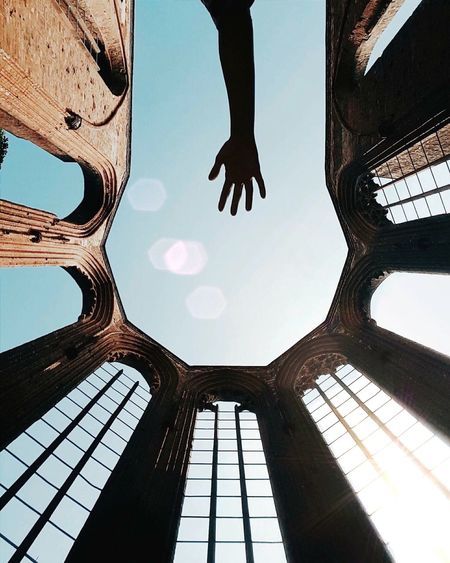 Cropped Image Of Silhouette Hand By Historic Built Structure Against Clear Sky