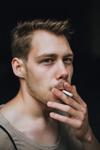 Young Man Smoking Cigarette Outdoors