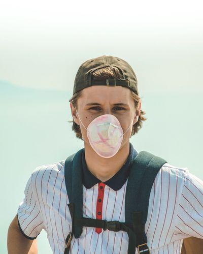 Portrait of teenage boy wearing mask against sky