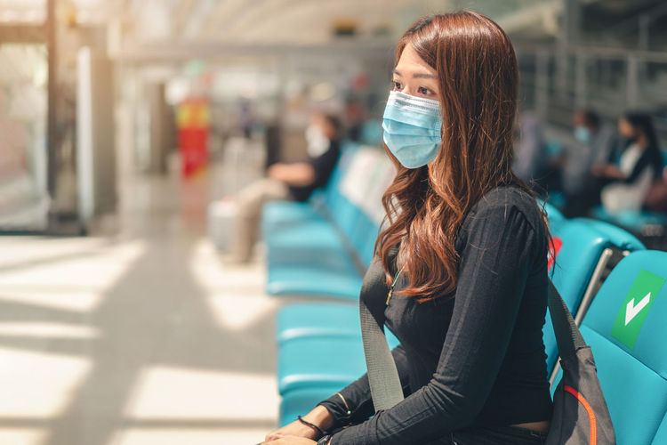 Woman wearing mask while sitting at airport