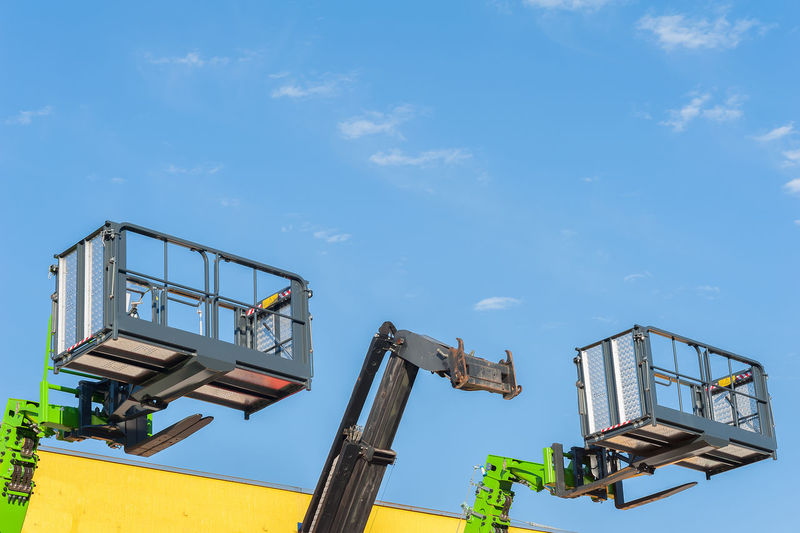 Low angle view lifting platforms against sky