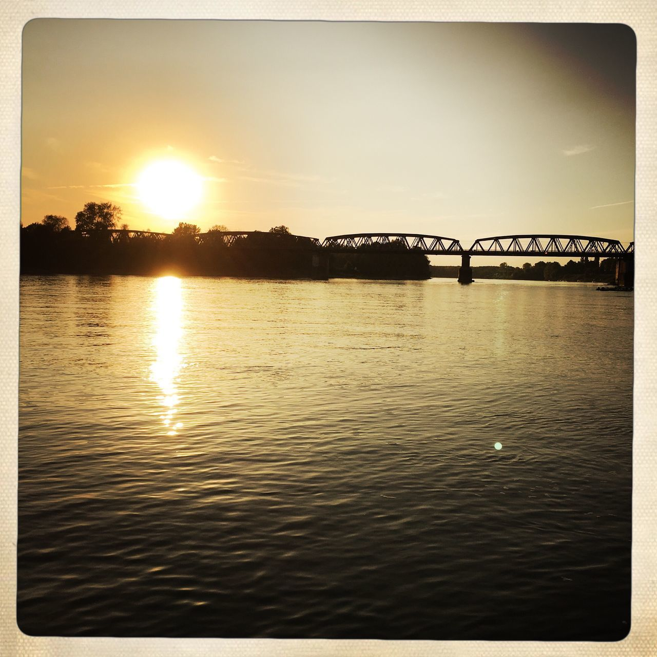 sunset, bridge - man made structure, connection, water, river, sunlight, sun, reflection, outdoors, no people, sky, silhouette, architecture, nature, built structure, beauty in nature, scenics, day