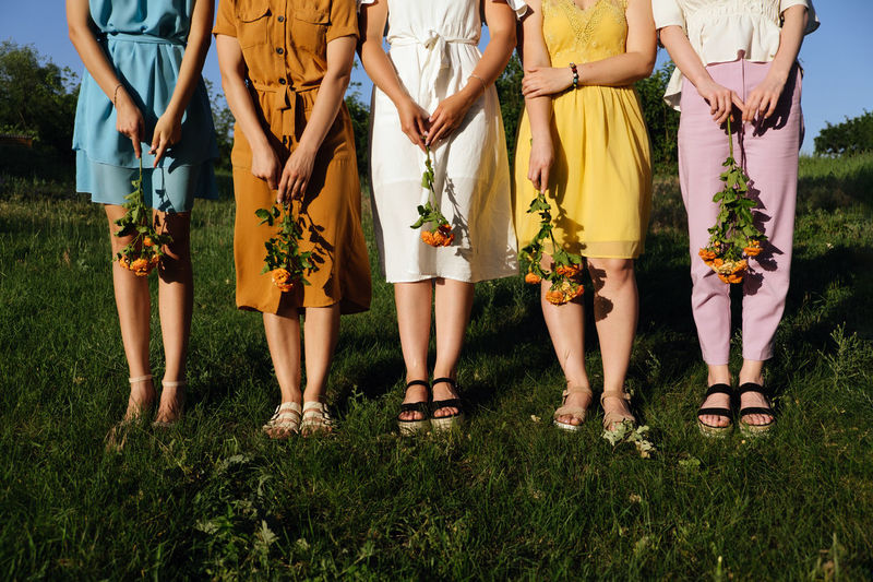 Womens diversity, girl power, femininity concept. group of five happy young women holding flowers