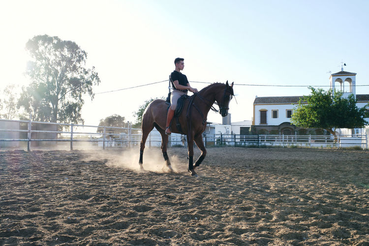 Man riding horse in ranch against sky