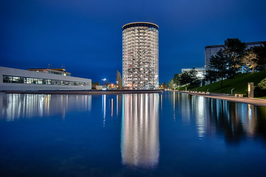 Tower Reflection Illuminated Travel Destinations Modern No People Outdoors Architecture Architecture_collection Germany Lights Cars Wolfsburg Autostadt Colourful Waterfront Europe Cityscape City Skyscraper Wide Angle Blue Hour Car Parking Car Park Architecture