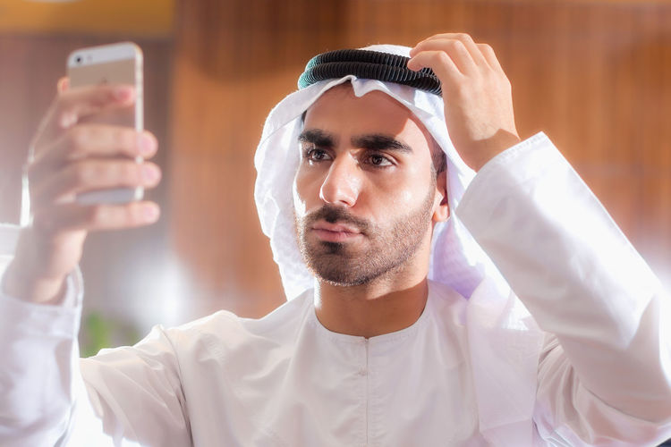 Close-up of man in traditional clothing taking selfie over smart phone