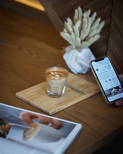 Coffee on Wooden Table with Book in Cafe Ijas Muhammed Photography Table Food And Drink Wood - Material Drink Refreshment Indoors  High Angle View Drinking Glass Household Equipment Still Life Cup Freshness No People Glass Wireless Technology Food Mug Coffee Cup Coffee - Drink Tray