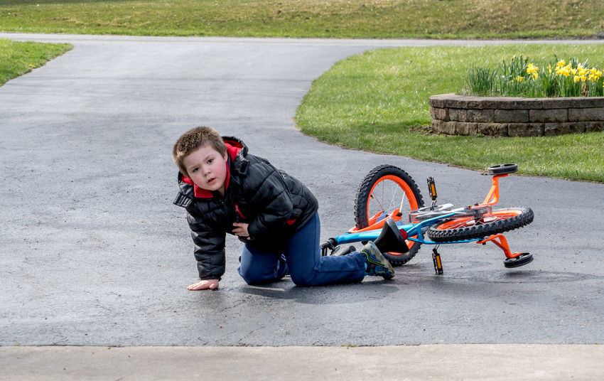 a young boy looks up from falling off his first bike. im ok! Learning Nature Outdooors Youth Accidents And Disasters Active Kids Bike Boy Bycicle Casual Clothing Caucasian Child Childhood Driveway Fall Falling Off A Bike Ground Hurt Kid Male Training Wheels Two Wheeler Riding Cycling