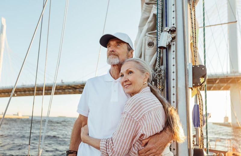 Senior couple on boat at sea against sky