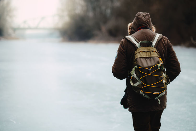Rear View Of Man In Warm Clothes With Backpack Walking On Snowfield