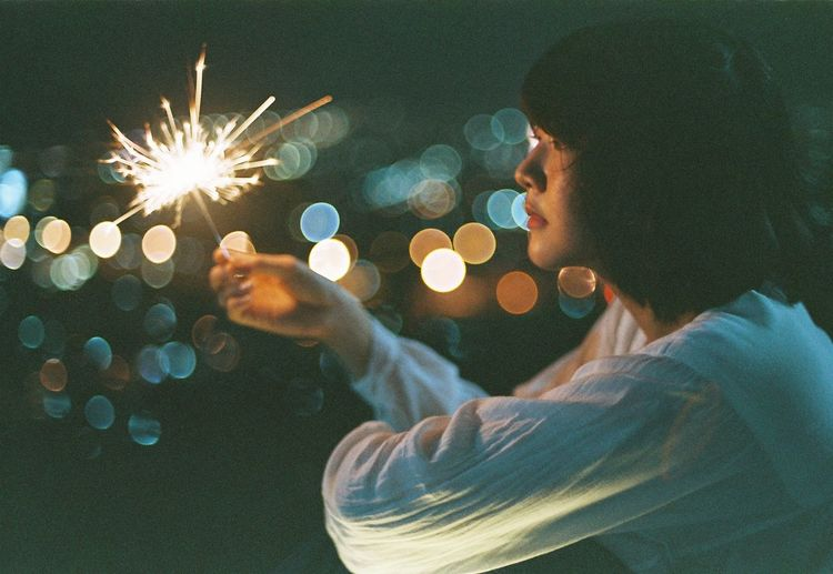 Young woman holding sparkler at night