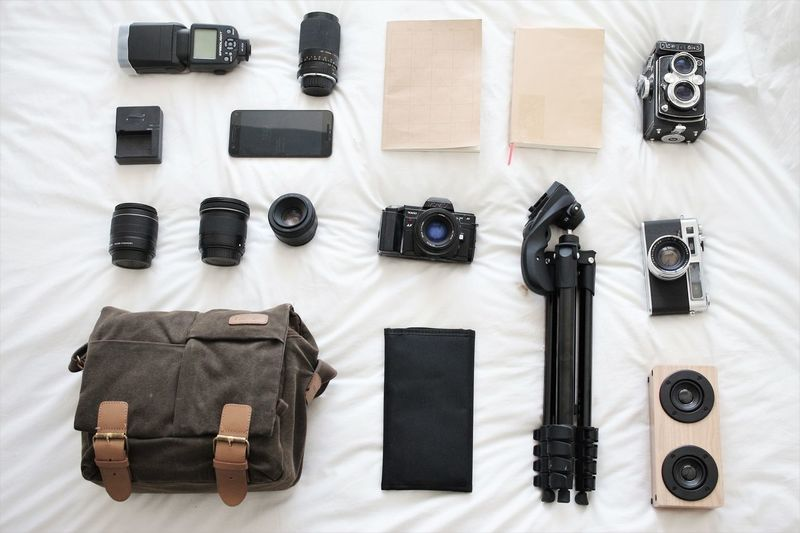 camera gear laid out in grid Camera Grid Arrangement Bag Black Color Camera - Photographic Equipment Camera Gear Close-up Day Directly Above Film Camera Group Of Objects High Angle View Indoors  Large Group Of Objects Lens Luggage Photography Themes Press Conference Suitcase Technology Tripod Variation Vintage Camera White Background