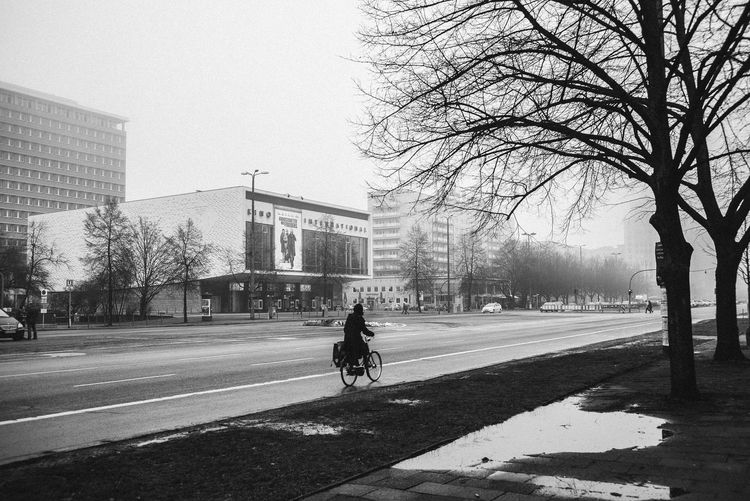 Adult Architecture Bare Tree Bike Blackandwhite Blackandwhite Photography Building Exterior Built Structure City Day Foggy Weather Karl Marx Allee Land Vehicle Men One Person Outdoors People Road Sky Stralauer Allee Street Transportation Tree Tree Woman On Bike
