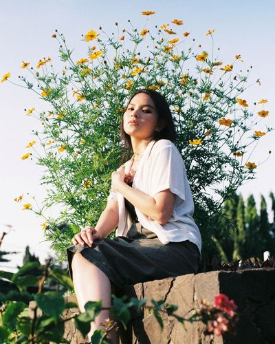 Young woman sitting against plants and trees against sky