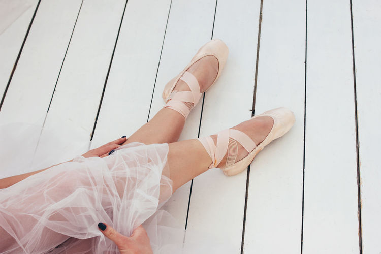 Low section of woman wearing ballet shoes while sitting on wooden floor