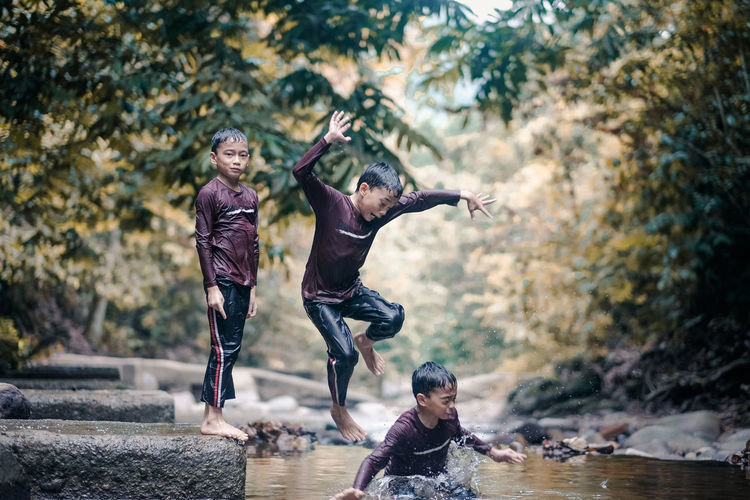 Multiple image of boy jumping into river in forest
