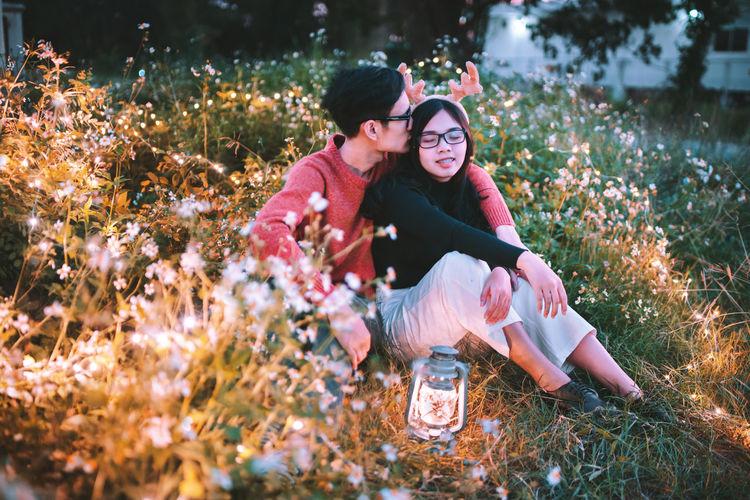 Man Kissing On Girlfriend Head Amidst Flowering Plants