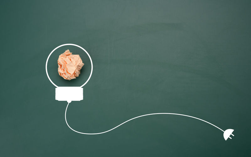 Crumpled sheet of paper on a green background, shape of a light bulb. energy saving concept, new