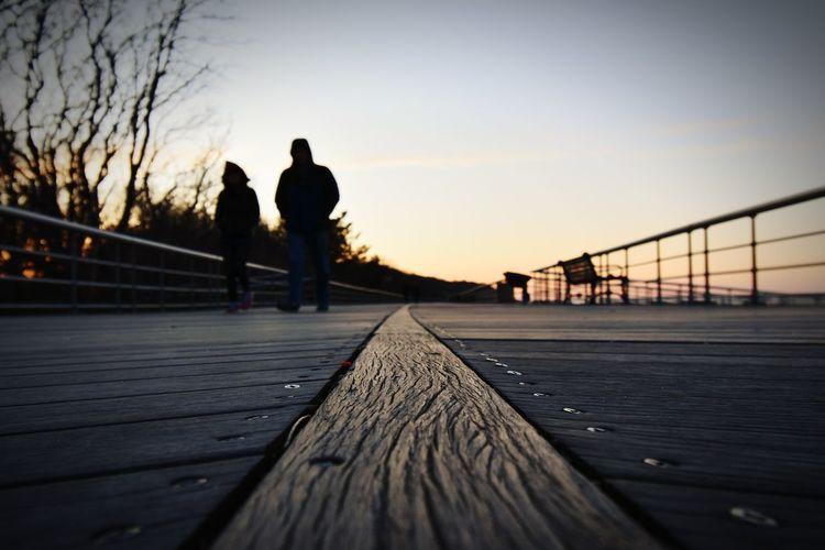 Sunset walk, relaxing board walking, couple walking,wood texture