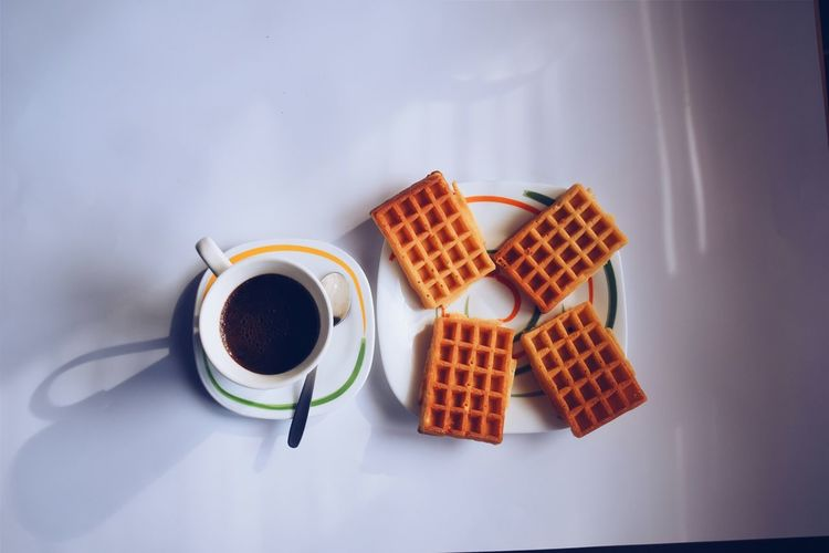 High Angle View Of Coffee With Waffles Served On Table