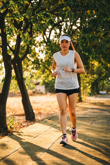 Woman runner does jogging on the city road. Sport and workout. Sport Workout Jogging Running Exercise One Person Full Length Real People Plant Tree Young Adult Lifestyles Leisure Activity Front View Casual Clothing Sunlight Day Nature Footpath Young Women Fashion Portrait Standing Outdoors Shorts Beautiful Woman Hairstyle Teenager