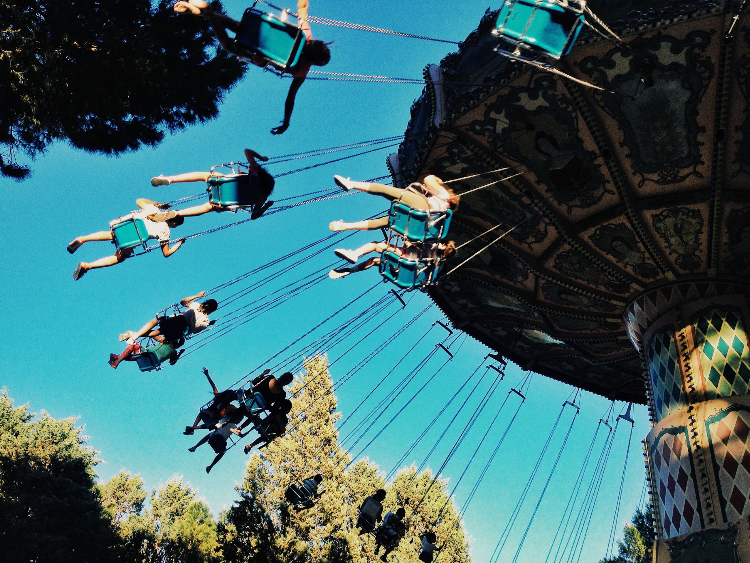 low angle view, tree, amusement park, arts culture and entertainment, amusement park ride, building exterior, clear sky, built structure, architecture, leisure activity, ferris wheel, sky, fun, enjoyment, blue, hanging, outdoors, large group of people, chain swing ride