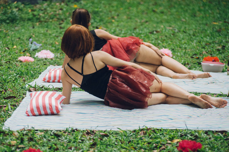 Bonding Childhood Day Field Full Length Grass Leisure Activity Lifestyles Lying Down Nature Outdoors Real People Rear View Relaxation Sitting The Photojournalist - 2017 EyeEm Awards Togetherness Two People Women Young Adult Young Women Breathing Space