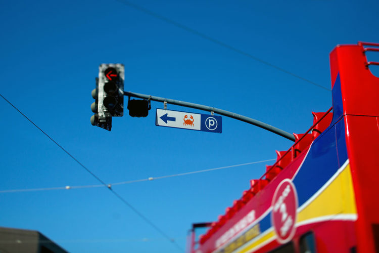 Low angle view of road signal and building against blue sky