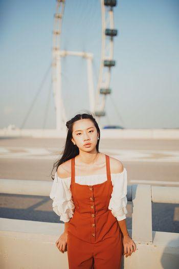 Portrait of woman standing against ferris wheel